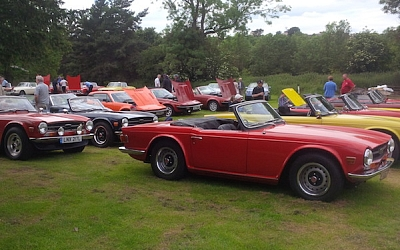The packed TR6 competition area with cars carefully parked to attract most voting attention.  Mick carefully inspecting exhausts, finger at the ready.